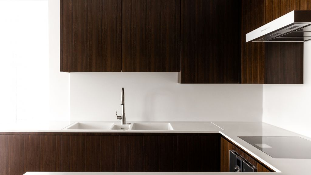 Ebony veneer kitchen design with Corian work surfaces